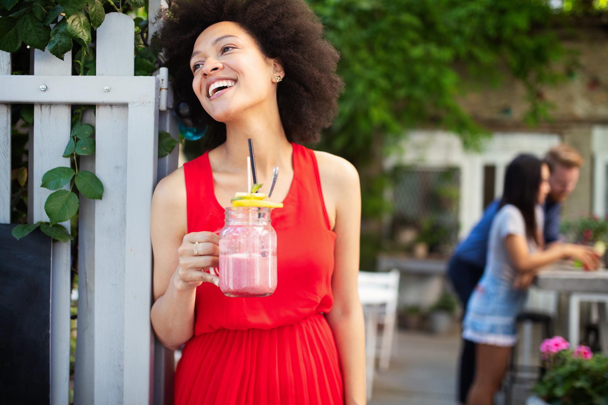 Woman laughing while enjoying smoothie