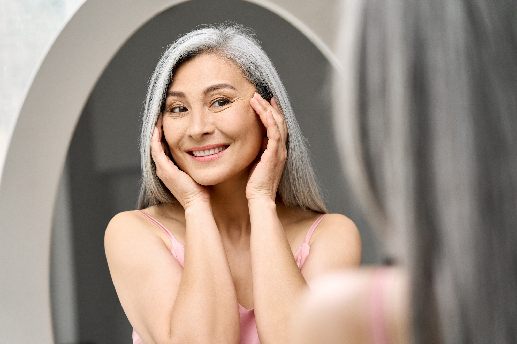 Happy mid aged Asian woman looking at self in mirror