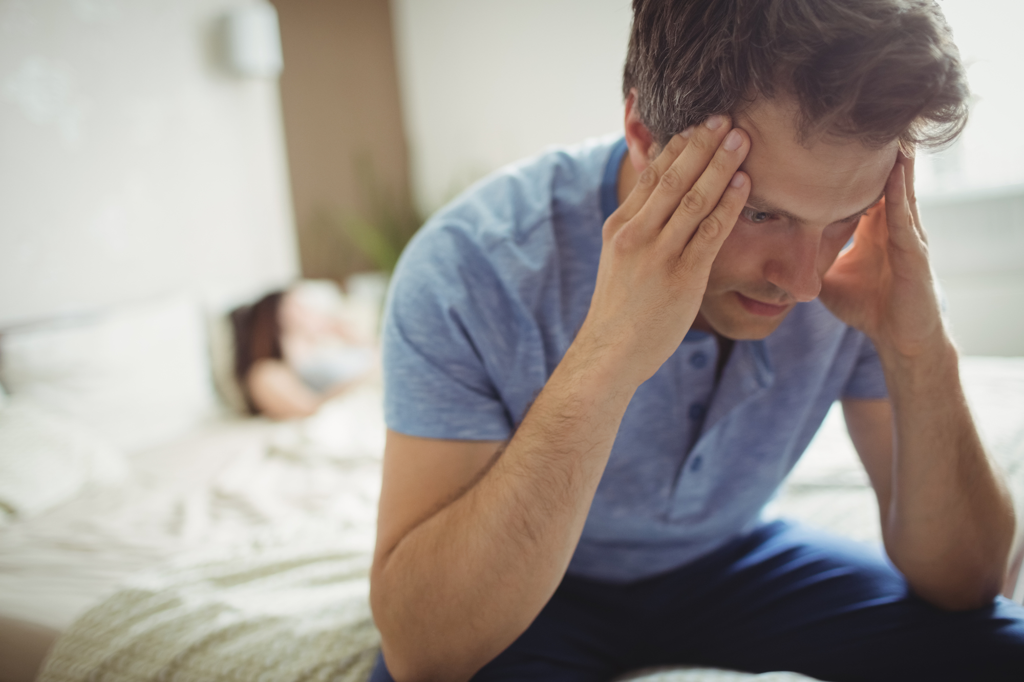 Man sitting at edge of bed upset with head in hands