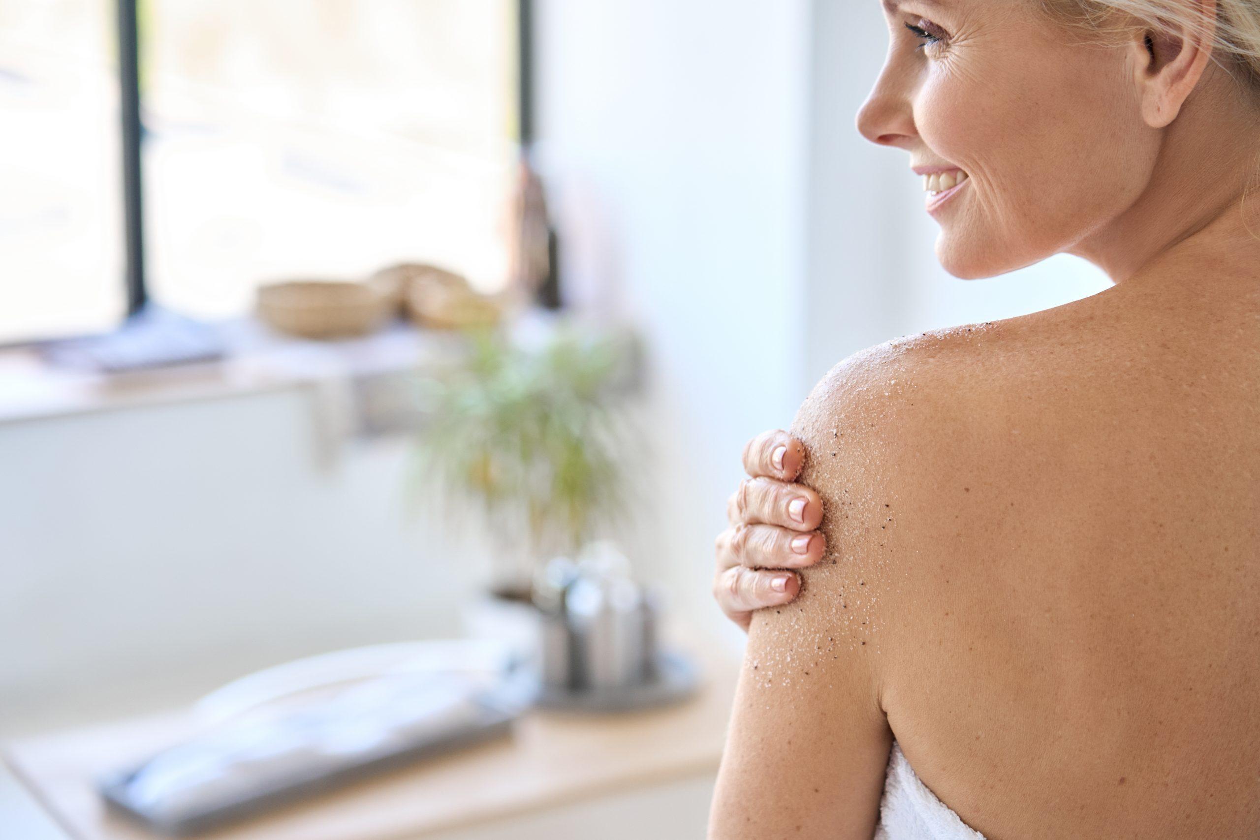 Back view of mid age woman applying body scrub