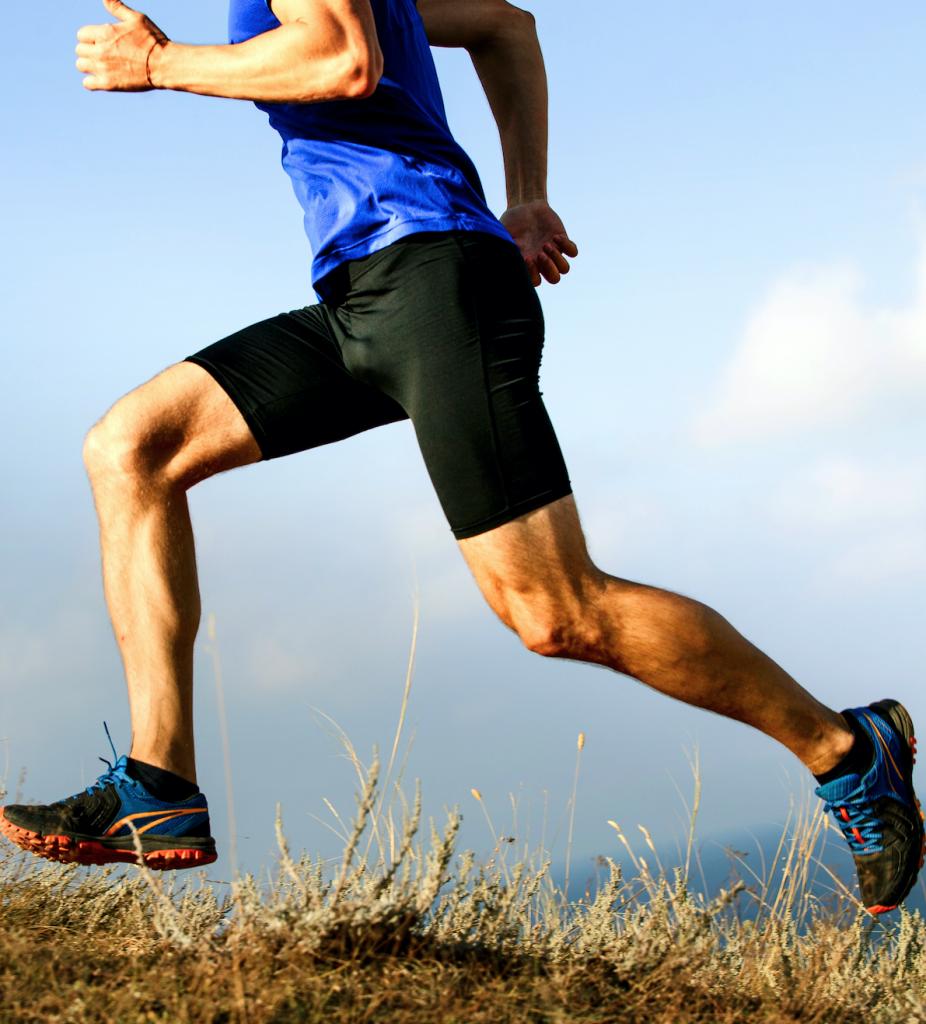 Athletic man running up grassy hill