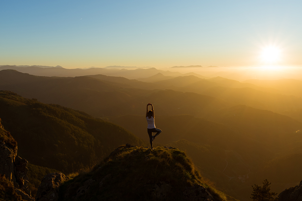 Woman doing a yoga pose on a mountain, thinking about the benefits of peptides