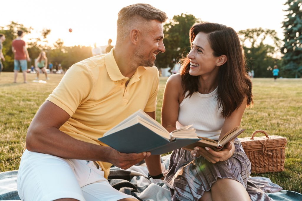 Portrait of joyful middle-aged couple man and woman smiling and reading books together during picnic in summer park