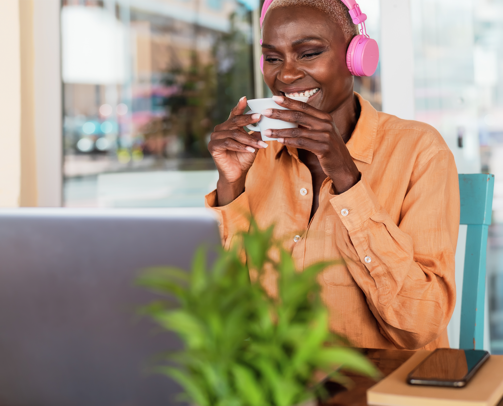 Black middle-aged woman laughing white drinking tea