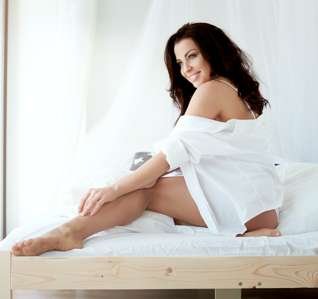 Woman in sexy white shirt smiling on bed