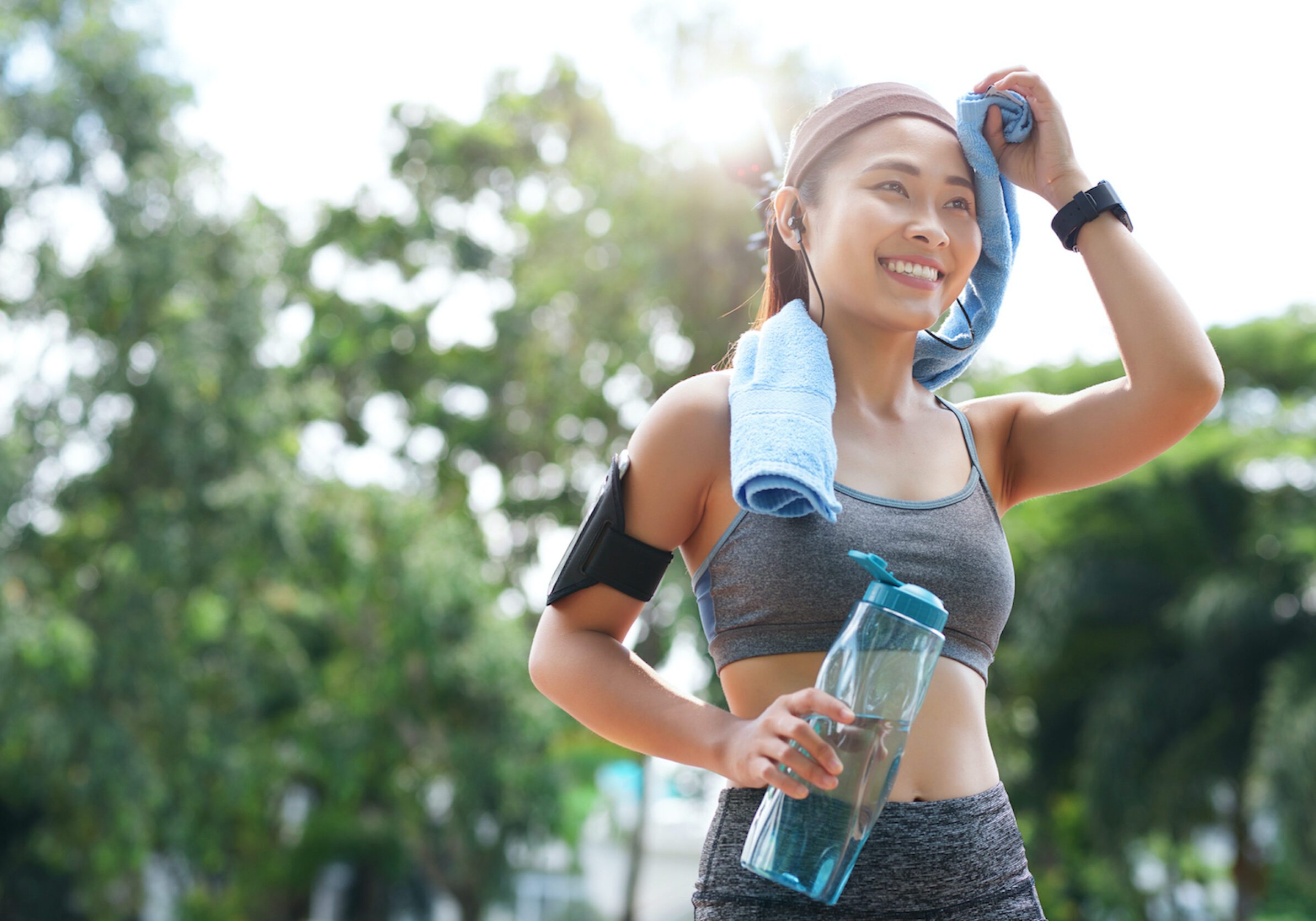 Cheerful sportswoman with bottle and towel