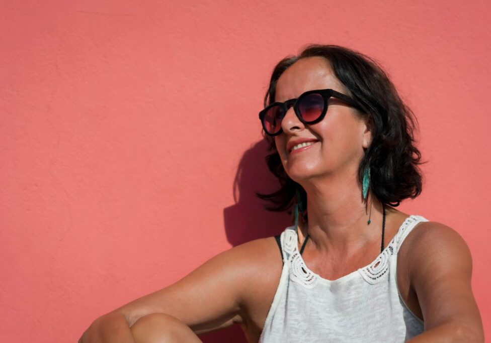 Beautiful mature woman suntanned wearing sunglasses leaning against a pink monochrome wall smiling.