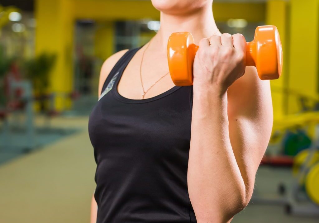fit-girl-exercising-with-dumbbells-muscular-woman--PLVVPB5