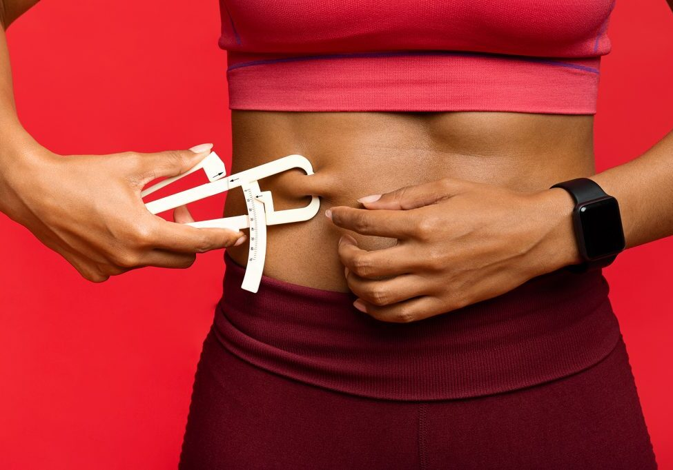woman-measuring-her-body-fat-with-body-fat-caliper-V4YBVRG